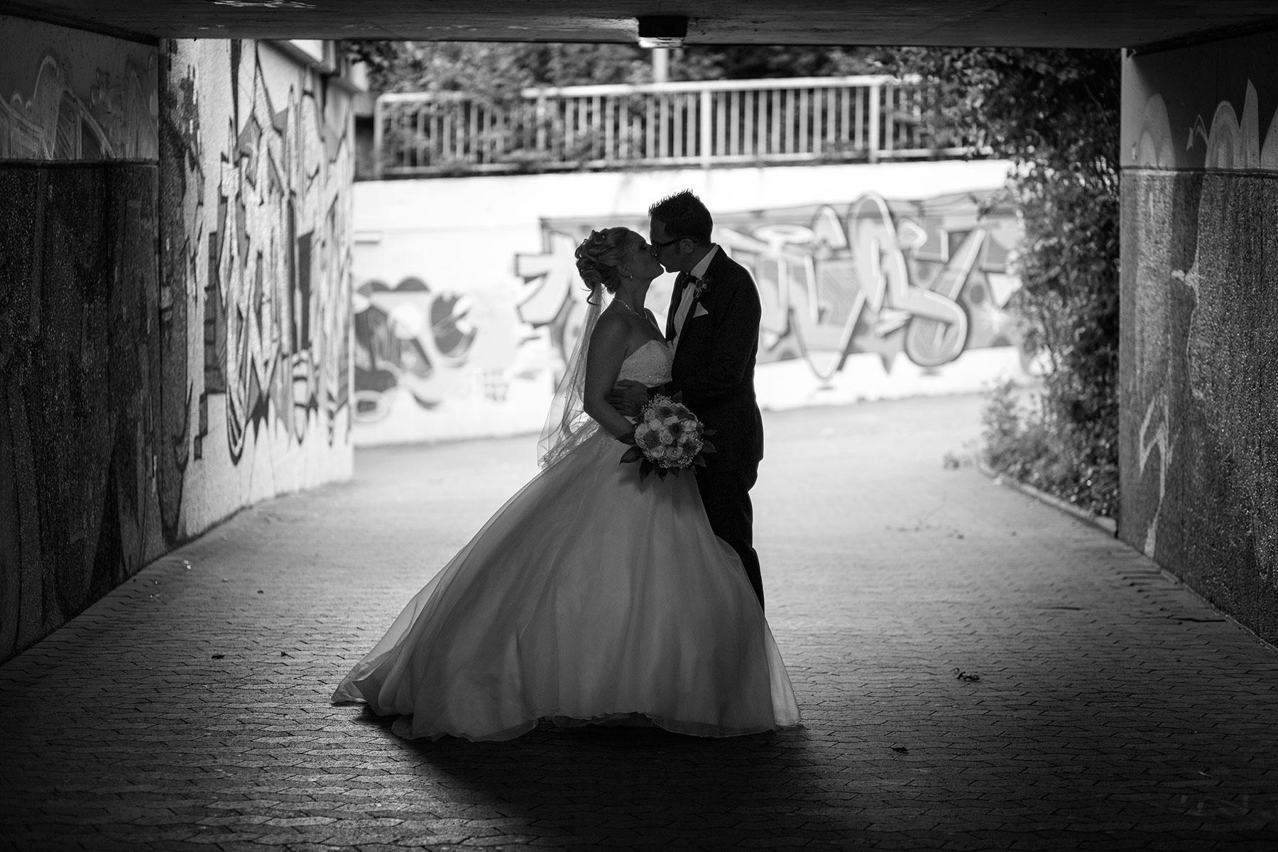 Schwarzweisses Hochzeitsfoto, Paar küsst sich unter einer Unterführung